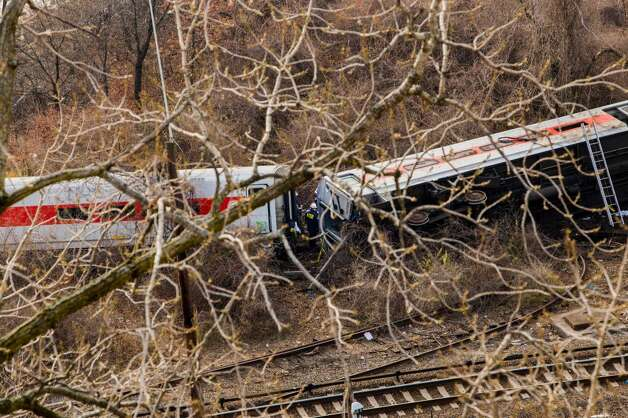 NEW YORK, NY - DECEMBER 1:  National Transportation Board (NTSB) workers look over the wreckage after a Metro-North commuter train derailed just north of the Spuyten Duyvil station December 1, 2013 in the Bronx borough of New York City. Multiple injuries and at least 4 deaths were reported after the seven car train left the tracks as it was heading to Grand Central Terminal along the Hudson River line.  (Photo by Christopher Gregory/Getty Images) ORG XMIT: 453423805 Photo: Christopher Gregory, Getty