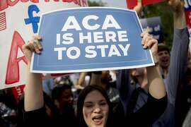 "A demonstrator in support of U.S. President Barack Obama's health-care law, the Affordable Care Act (ACA), holds up a ""ACA is Here to Stay"" sign after the U.S. Supreme Court ruled 6-3 to save Obamacare tax subsidies outside the Supreme Court in Washington, D.C., U.S., on Thursday, June 25, 2015. The U.S. Supreme Court upheld the nationwide tax subsidies that are a core component of President Barack Obama's health-care law rejecting a challenge that had threatened to gut the measure and undercut his legacy. Photographer: Andrew Harrer/Bloomberg"