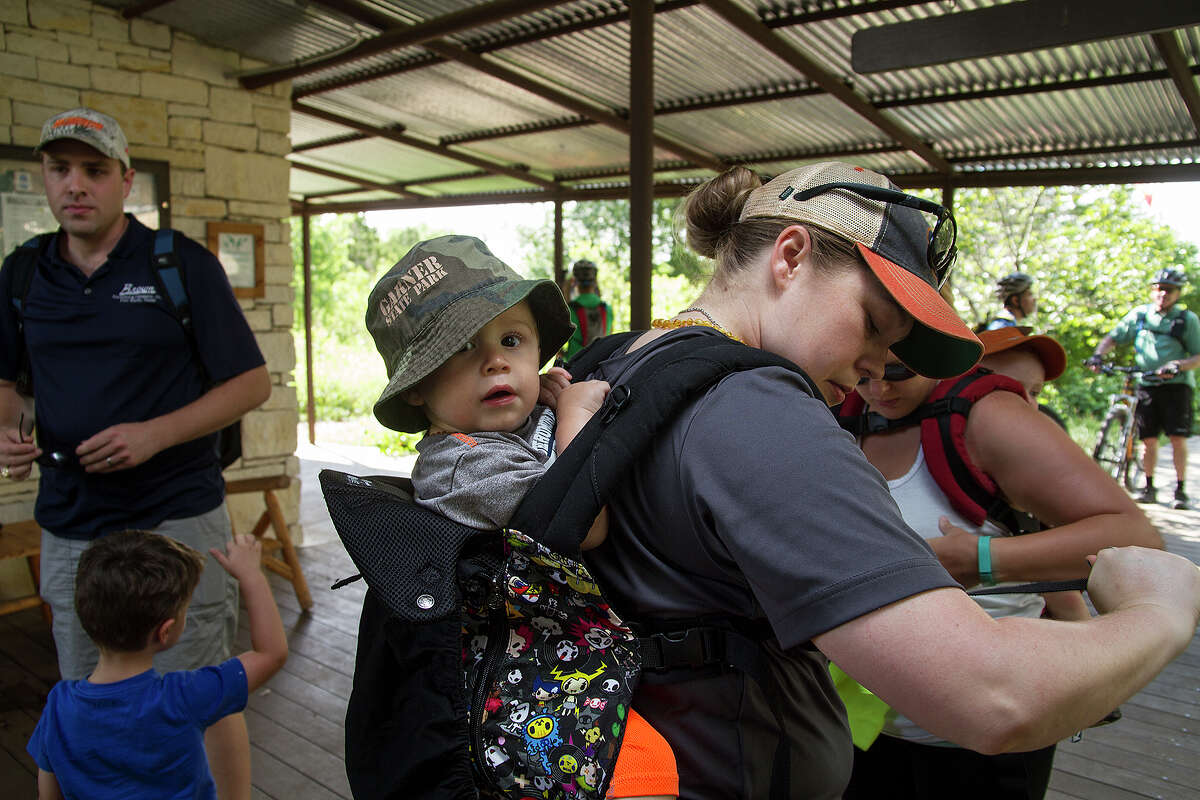 Kristin Zapata carries her one year-old baby Michael, as they get ready for at Government Canyon State Natural Area, Saturday, June 6, 2015 with the group Hike It Baby.