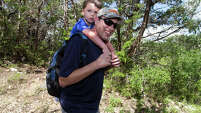Travis Cody carries his 3 1/2 year-old son Cason as they hike in Government Canyon State Natural Area with the Hike it Baby group, Saturday, June 6, 2015.