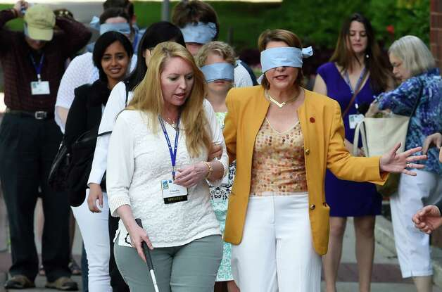 Dr. Claudia Folska, left, who is sight impaired, takes Saratoga Mayor Joanne Yepsen for a walk on Broadway with other attendees of the American Planning Association convention Thursday morning, June 25, 2015, in Saratoga Springs, N.Y. The experience was intended to give participants an understanding of how sight impaired pedestrians have to navigate city streets. (Skip Dickstein/Times Union) Photo: SKIP DICKSTEIN