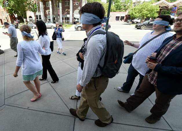 Blindfolded participants in the American Planning Association convention walk on Broadway Thursday morning, June 25, 2015, in Saratoga Springs, N.Y. The experience was intended to give participants an understanding of how sight impaired pedestrians have to navigate city streets. (Skip Dickstein/Times Union) Photo: SKIP DICKSTEIN