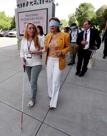 Claudia Folska, left, who is sight impaired, takes Saratoga Mayor Joanne Yepsen for a walk on Broadway Thursday morning, June 25, 2015, in Saratoga Springs, N.Y. The experience was intended to give participants an understanding of how sight impaired pedestrians have to navigate city streets. (Skip Dickstein/Times Union) Photo: SKIP DICKSTEIN