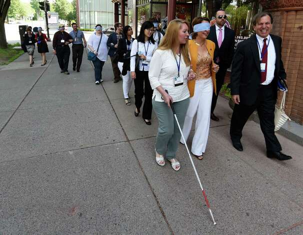 Claudia Folska, left, who is sight impaired, takes Saratoga Mayor Joanne Yepsen for a walk on Broadway with other attendees of the American Planning Association convention Thursday morning, June 25, 2015, in Saratoga Springs, N.Y. The experience was intended to give participants an understanding of how sight impaired pedestrians have to navigate city streets. (Skip Dickstein/Times Union) Photo: SKIP DICKSTEIN