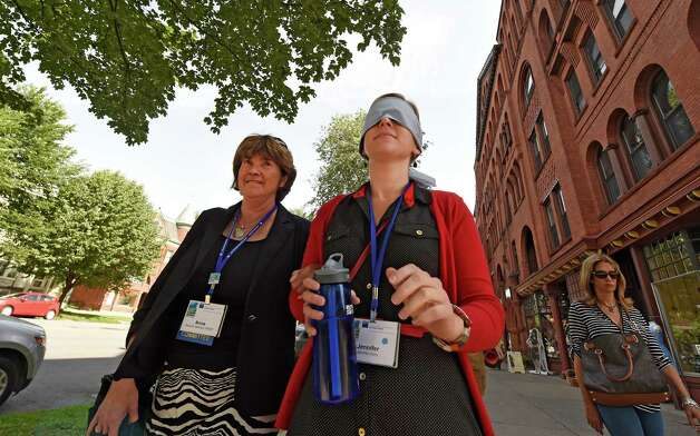 Anna Breinick, planner from Brunswick, Maine, left, takes Jennifer Horn a planner from Harrisburg, Pa. for a walk on Broadway with other attendees of the American Planning Association convention Thursday morning, June 25, 2015, in Saratoga Springs, N.Y. The experience was intended to give participants an understanding of how sight impaired pedestrians have to navigate city streets. (Skip Dickstein/Times Union) Photo: SKIP DICKSTEIN