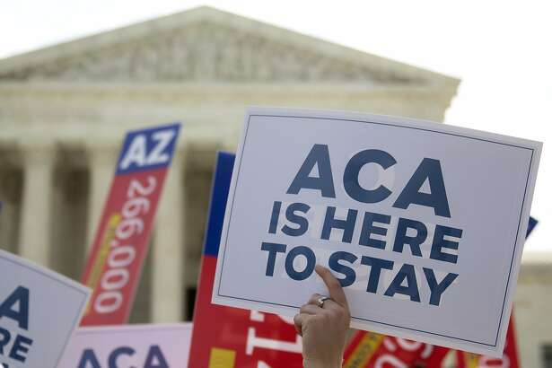 """A demonstrator in support of U.S. President Barack Obama's health-care law, the Affordable Care Act (ACA), holds up a """"ACA is Here to Stay"""" sign after the U.S. Supreme Court ruled 6-3 to save Obamacare tax subsidies outside the Supreme Court in Washington, D.C., U.S., on Thursday, June 25, 2015. The U.S. Supreme Court upheld the nationwide tax subsidies that are a core component of President Barack Obama's health-care law rejecting a challenge that had threatened to gut the measure and undercut his legacy. Photographer: Andrew Harrer/Bloomberg"""