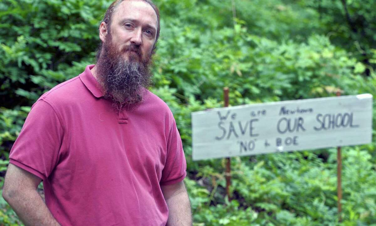 Aaron Cox stands at the end of the driveway to his Newtown home where he has put up signs asking that the Hawley Elementary School not be closed.