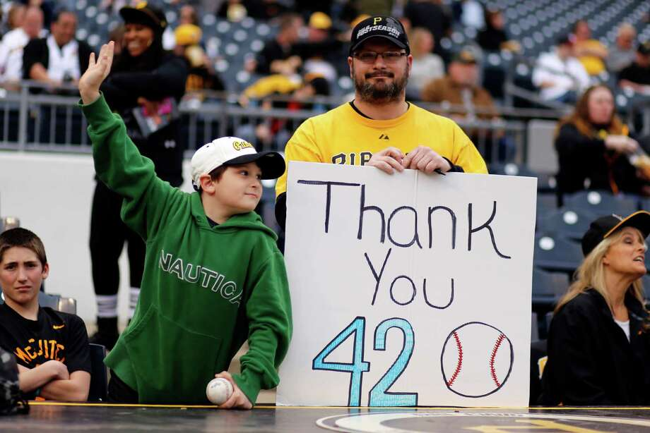 Pittsburgh Pirates fans hold a sign honoring Jackie Robinson as they watch pre-game warm ups before a baseball game between the Pittsburgh Pirates and the Detroit Tigers in Pittsburgh Wednesday, April 15, 2015.(AP Photo/Gene J. Puskar) Photo: Gene J. Puskar, STF / Associated Press / AP