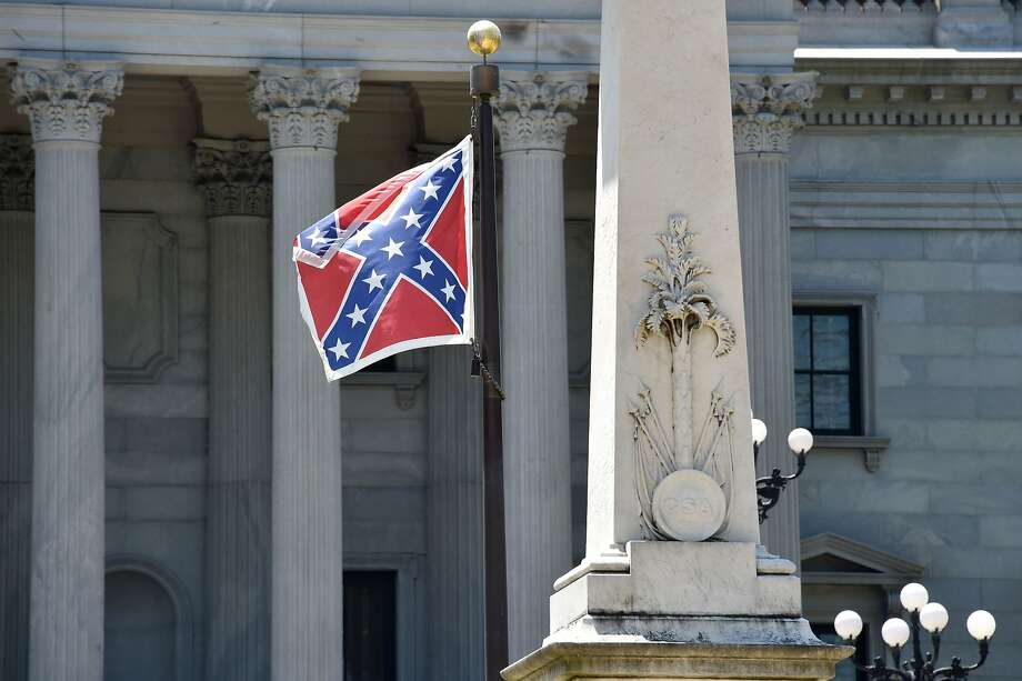 The Confederate flag is seen waving behind the monument of the victimes of the Confederation Army during the American Civil War in front of the State Congress building in Columbia, South Carolina on June 19, 2015. Police captured the white suspect in a gun massacre at one of the oldest black churches in Charleston in the United States, the latest deadly assault to feed simmering racial tensions. Police detained 21-year-old Dylann Roof, shown wearing the flags of defunct white supremacist regimes in pictures taken from social media, after nine churchgoers were shot dead during bible study on Wednesday. AFP PHOTO/MLADEN ANTONOVMLADEN ANTONOV/AFP/Getty Images Photo: Mladen Antonov, AFP / Getty Images