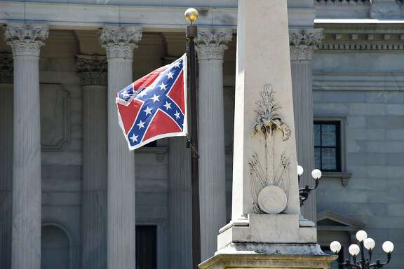 The Confederate flag is seen waving behind the monument of the victimes of the Confederation Army during the American Civil War in front of the State Congress building in Columbia, South Carolina on June 19, 2015. Police captured the white suspect in a gun massacre at one of the oldest black churches in Charleston in the United States, the latest deadly assault to feed simmering racial tensions. Police detained 21-year-old Dylann Roof, shown wearing the flags of defunct white supremacist regimes in pictures taken from social media, after nine churchgoers were shot dead during bible study on Wednesday. AFP PHOTO/MLADEN ANTONOVMLADEN ANTONOV/AFP/Getty Images