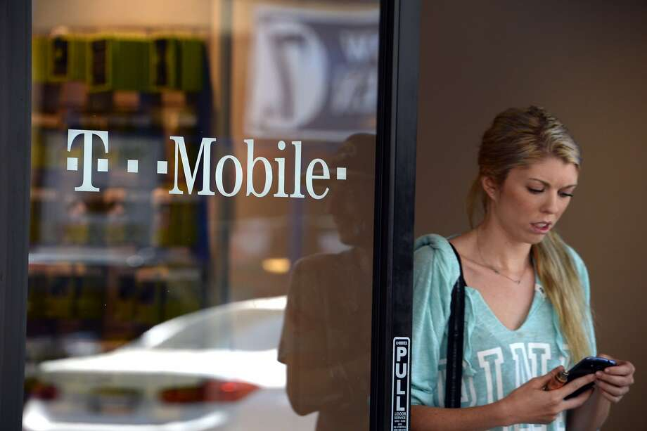 FILE - JUNE 3, 2015: According to reports, Dish Network is currently in talks with T-Mobile for a merger. A patron exits a T-Mobile store in Glendale, California, on August 1, 2014. Shares in T-Mobile jumped on July 31 on a report that French telecommunications firm Iliad is bidding to buy the US wireless service carrier.   AFP PHOTO / Robyn Beck        (Photo credit should read ROBYN BECK/AFP/Getty Images) Photo: Robyn Beck