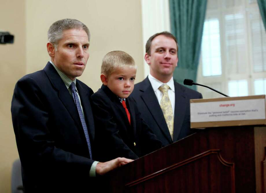 Carl Krawitt, left,  a supporter of a measure requiring nearly all of California school children to be vaccinated, answers a question during news conference at the Capitol in Sacramento, Calif., Wednesday, April 15, 2015. Krawitt's said he had worried about son Rhett, 7, center, who was unable to be vaccinated while receiving treatment for leukemia. At right is Assemblyman Marc Levine,B-San Rafeal, a supporter of the measure and whose district the Krawitts live. The state Assembly is expected to vote on the bill, Thursday. (AP Photo/Rich Pedroncelli) Photo: Rich Pedroncelli, STF / AP