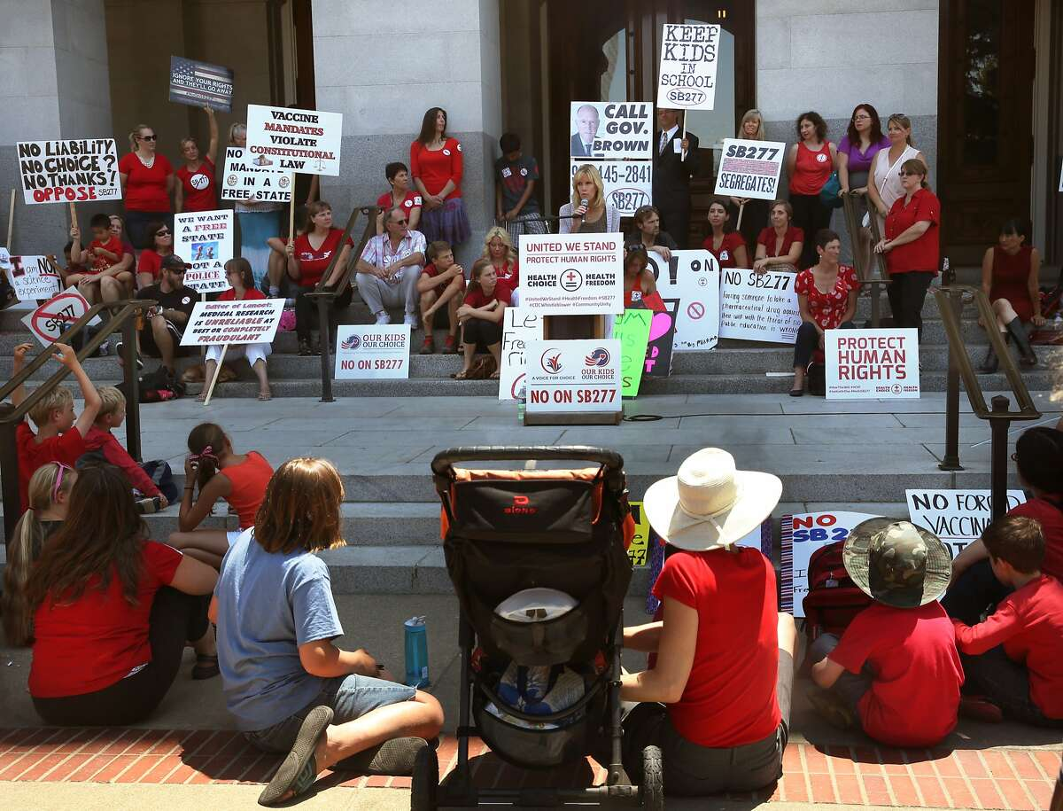 About a hundred people in front of the California state capitol building in Sacramento, Calif., protest as senate bill 277 passes on Thursday, June 25, 2015.