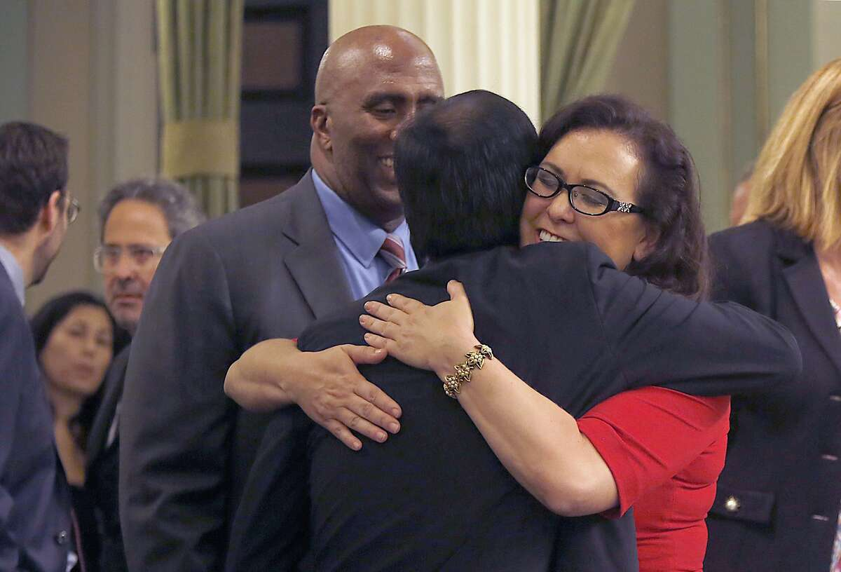Dr. Richard Pan, pediatrician and senator representing Sacramento, gets a hug from assembly woman Lorena Gonzalez, D-San Diego, as senate bill 277 is passed at the California state capitol building in Sacramento, Calif., on Thursday, June 25, 2015. Behind at left is assemblyman Jim Cooper, D-Elk Grove. This bill would end California's vaccine exemption loophole and boost immunization rates at California schools.