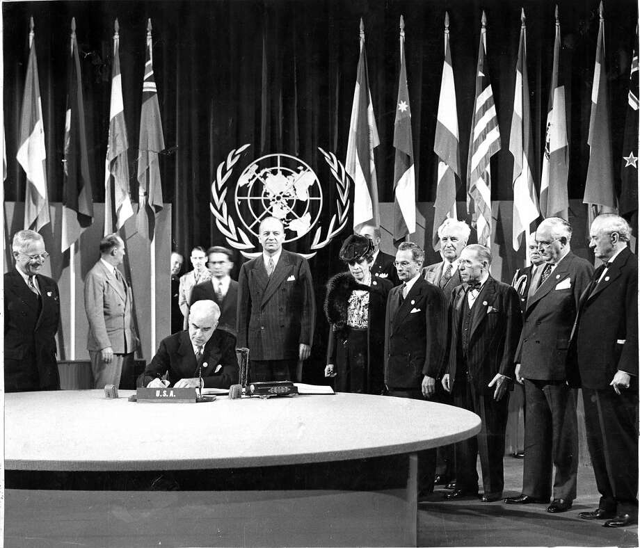 United Nations Charter Signing President Harry Truman watches as Secretary of State Stettinious signs the World Charter for the United States  Photo ran 06/27/1945, Pg 1 No credit information