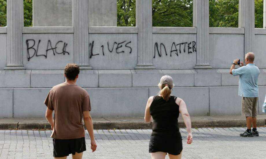 "A passerby photographs the spray painted message of ""Black Lives Matter"" that was painted on a monument to former Confederate President Jefferson Davis on Monument Avenue in Richmond, Va., Thursday, June 25, 2015.  The vandalism comes after a mass shooting in Charleston South Carolina has sparked a nationwide debate on the public display of Confederate imagery. (AP Photo/Steve Helber) Photo: Steve Helber, STF / AP"