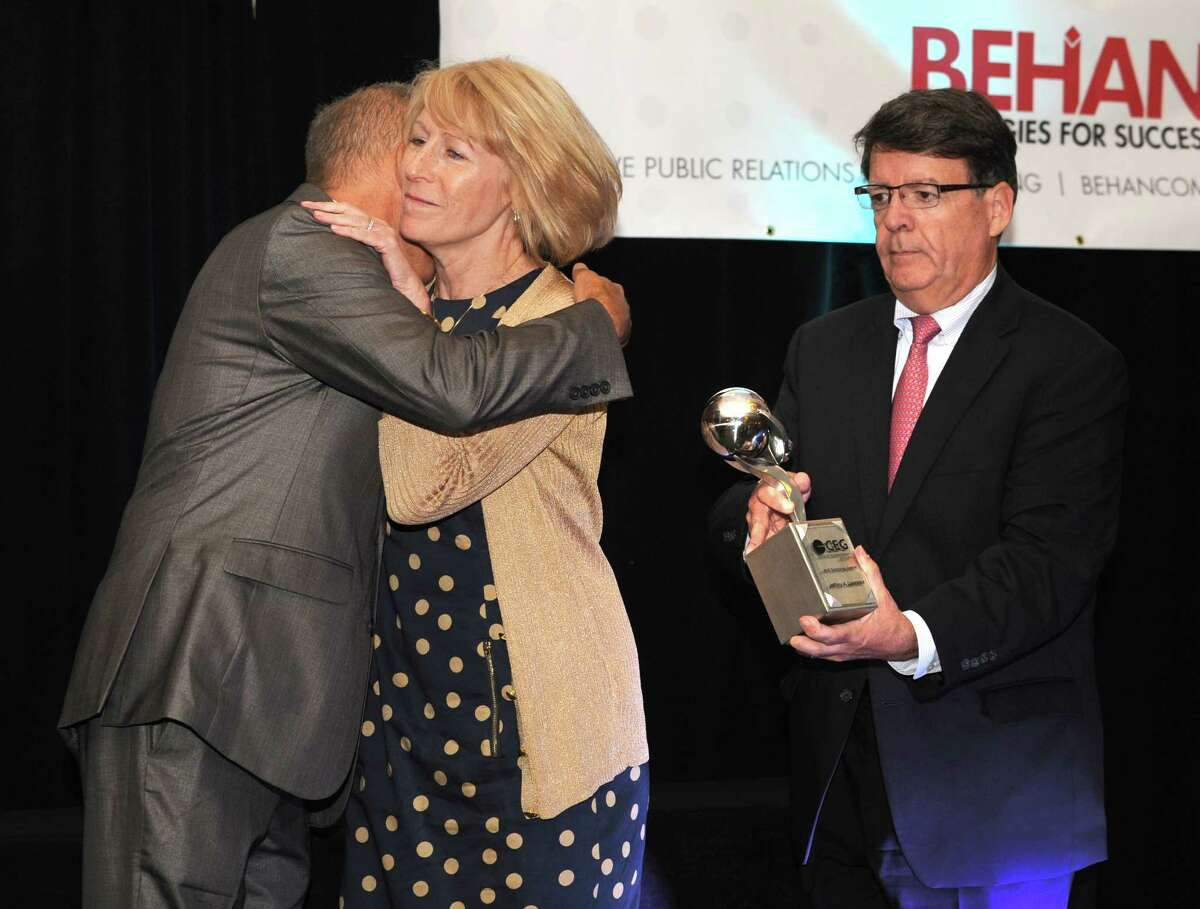 From left, Michael Hickey, Chair, Center for Economic Growth & Executive in Residence, Siena College, hugs Sharon Lawrence, as F. Michael Tucker, President & CEO of CEG holds a tribute award for her late husband Jeffrey Lawrence during the 19th Annual Technology Awards Luncheon at the Albany Marriott Hotel on Thursday, June 25, 2015 in Colonie, N.Y. Jeffrey Lawrence was the executive vice president for technology at CEG. (Lori Van Buren / Times Union)