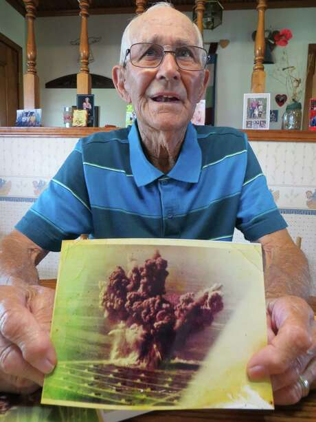 Louis Ehlinger Sr. of Devine recalls how he survived the Nov. 13, 1963, blast of high explosives stored at Medina Base Annex that broke windows in downtown San Antonio and created a mushroom cloud, which can be seen in a photo he displayed. Photo: Zeke MacCormack /San Antonio Express-News / San Antonio Express-News