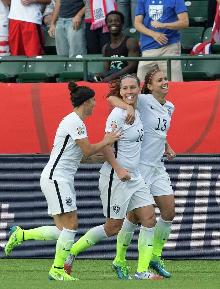 United States' Ali Krieger (11), Lauren Holiday (12) and Alex Morgan (13) celebrate a goal against Colombia during second half FIFA Women's World Cup round of 16 soccer action in Edmonton, Alberta, Canada, Monday, June 22, 2015.  (Jason Franson/The Canadian Press via AP) MANDATORY CREDIT ORG XMIT: EDM122 Photo: JASON FRANSON / CP