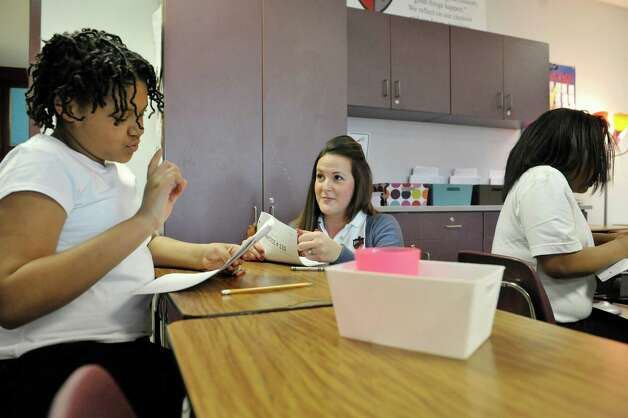 Fifth grader Sydney Dudley, left, works with math teacher Sarah Appell, center, during class at KIPP Tech Valley middle school on Tuesday, March 31, 2015, in Albany, N.Y.  (Paul Buckowski / Times Union) Photo: PAUL BUCKOWSKI / 00031207A