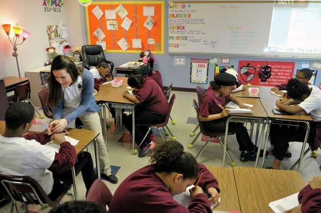 Fifth grade math teacher Sarah Appell, left, works with a student in class at KIPP Tech Valley middle school on Tuesday, March 31, 2015, in Albany, N.Y.  (Paul Buckowski / Times Union) Photo: PAUL BUCKOWSKI / 00031207A