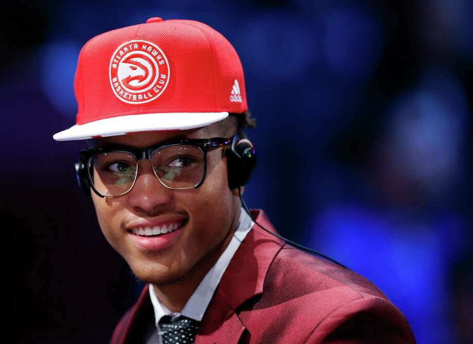 Despite his eyewear, seeing isn't believing when it comes to Kelly Oubre Jr. as the Hawks hat he was wearing after being selected 15th gave way to Wizards gear when his rights were traded to Washington. Photo: Kathy Willens, STF / AP