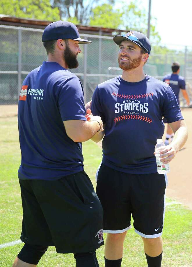 Sonoma Stompers pitcher Sean Conroy, right, gets a handshake from catcher Isaac Wenrich during practice at Arnold Field, in Sonoma, Calif., on Tuesday, June 23, 2015.  Conroy, 23, of Clifton Park, N.Y., is the first openly gay player to enter the professional baseball ranks, according to the Stompers.   (Christopher Chung/ The Press Democrat via AP) ORG XMIT: CASRP101 Photo: Christopher Chung / The Press Democrat