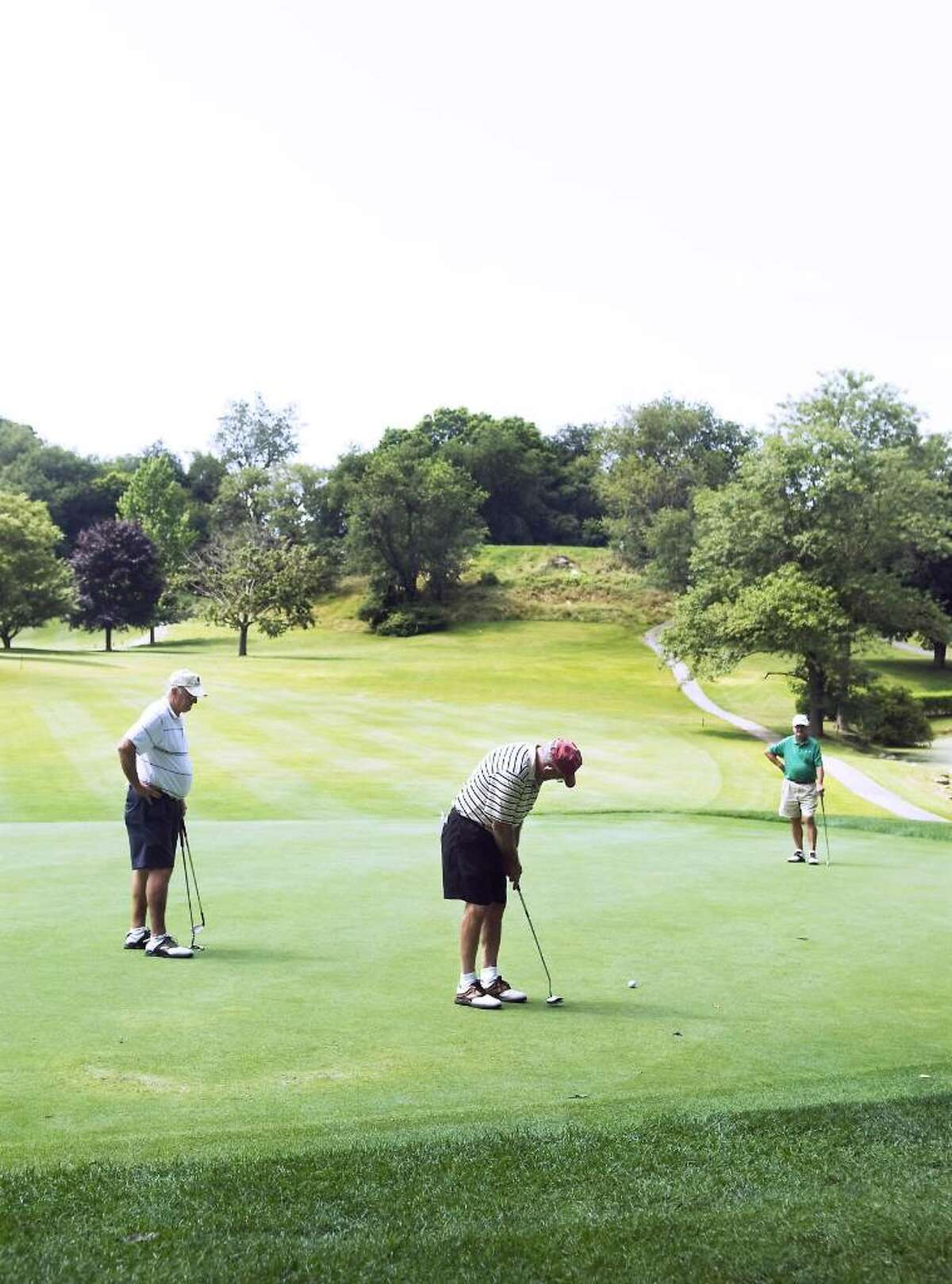 File photo of golfers as they tee off on the 13th hole at E. Gaynor Brennan Municipal Golf Course during the summer of 2009. Before taking a swing, donning those running shoes or planning a hike, it is important to make sure those muscles are ready for the motion, after a long winter's nap.