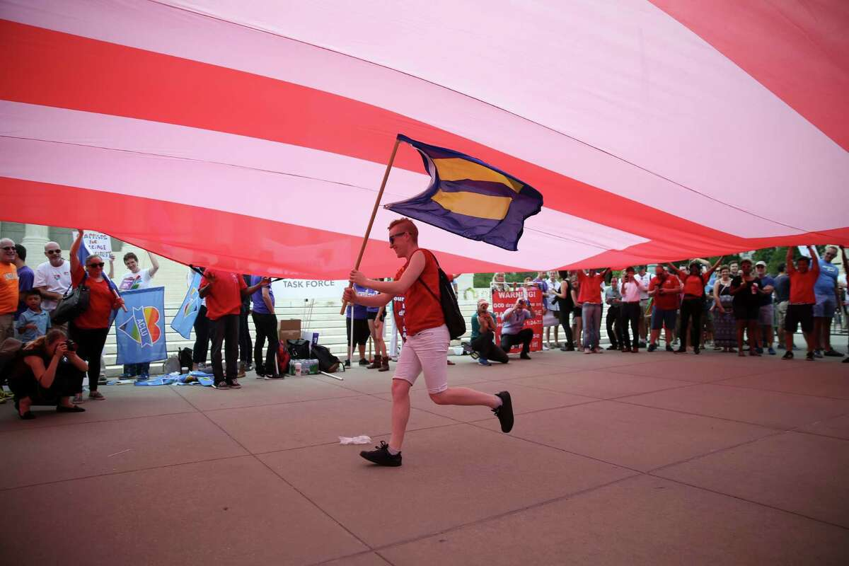 A demonstrator waves a flag with an equality sign while underneath a large flag with the same symbol held by other protesters outside the U.S. Supreme Court in Washington, June 26, 2015. The Supreme Court will rule soon on Obergefell v. Hodges and three related cases, which will decide whether the Constitution guarantees a right to same-sex marriage.