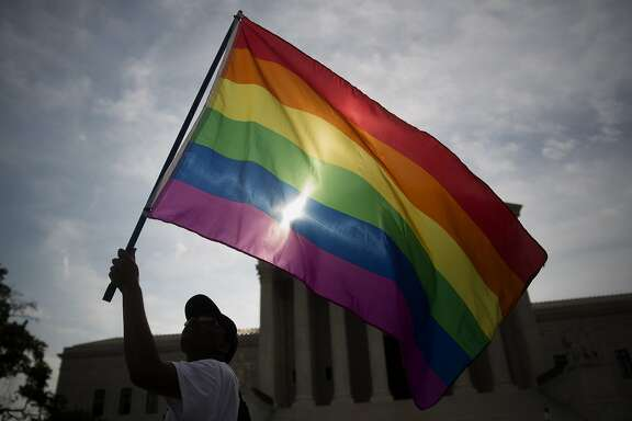 Demonstrator Carlos McKnight, from Washington, D.C., waves a rainbow flag outside the U.S. Supreme Court in Washington, D.C., U.S., on Friday, June 26, 2015. The high court will decide by the end of the month whether the Constitution gives gays the right to marry. The court's actions until now have suggested that a majority of the nine justices will vote to legalize same-sex weddings nationwide. Photographer: Andrew Harrer/Bloomberg *** Local Caption *** Carlos McKnight
