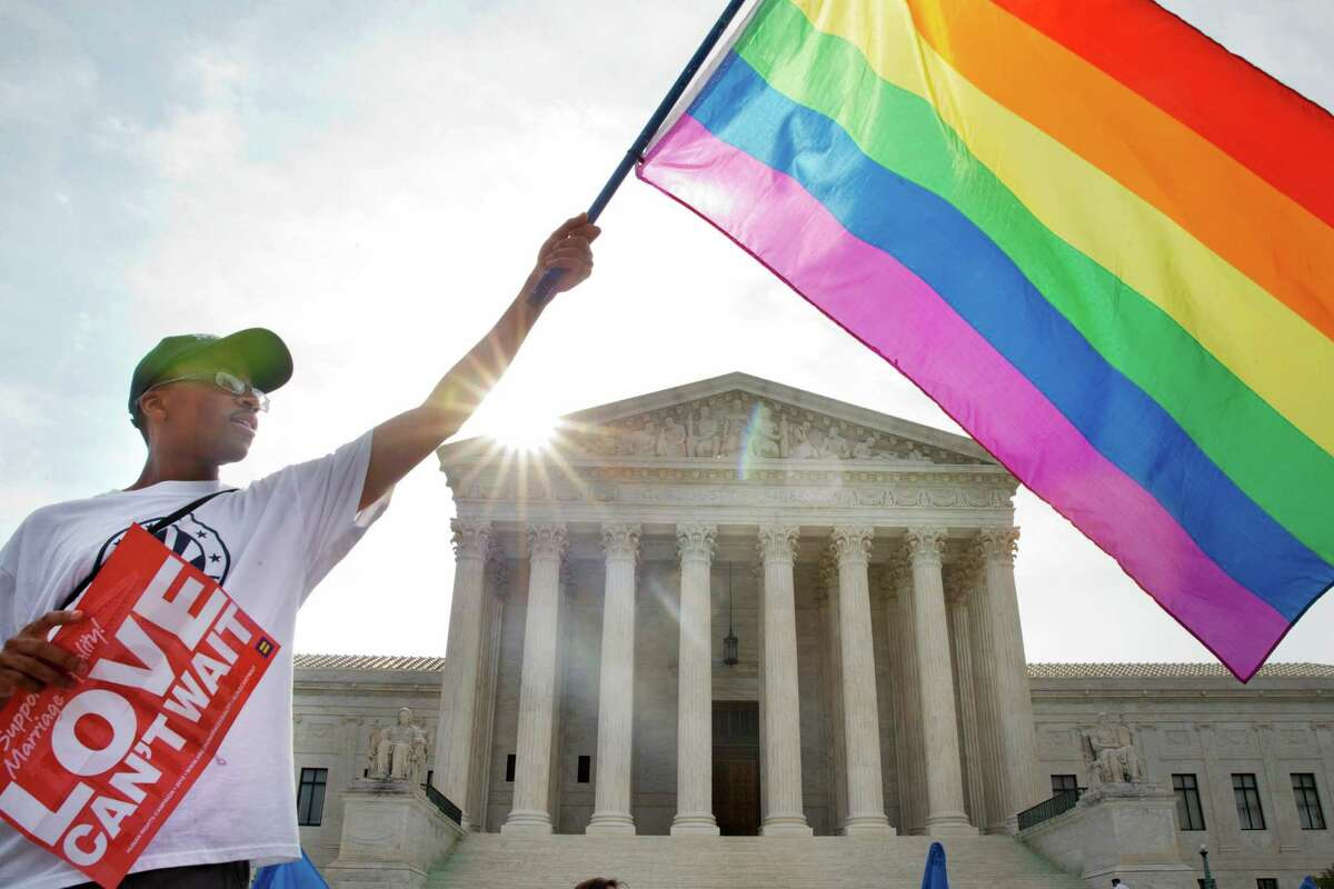 Carlos McKnight of Washington, waves a flag in support of gay marriage outside of the Supreme Court in Washington, Friday June 26, 2015. A major opinion on gay marriage is among the remaining to be released before the term ends at the end of June. (AP Photo/Jacquelyn Martin) ORG XMIT: DCJM109