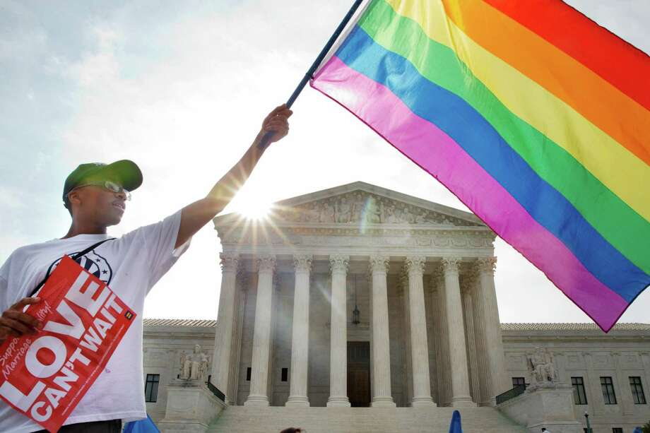 Carlos McKnight of Washington, waves a flag in support of gay marriage outside of the Supreme Court in Washington, Friday June 26, 2015. A major opinion on gay marriage is among the remaining to be released before the term ends at the end of June.  (AP Photo/Jacquelyn Martin) ORG XMIT: DCJM109 Photo: Jacquelyn Martin / AP