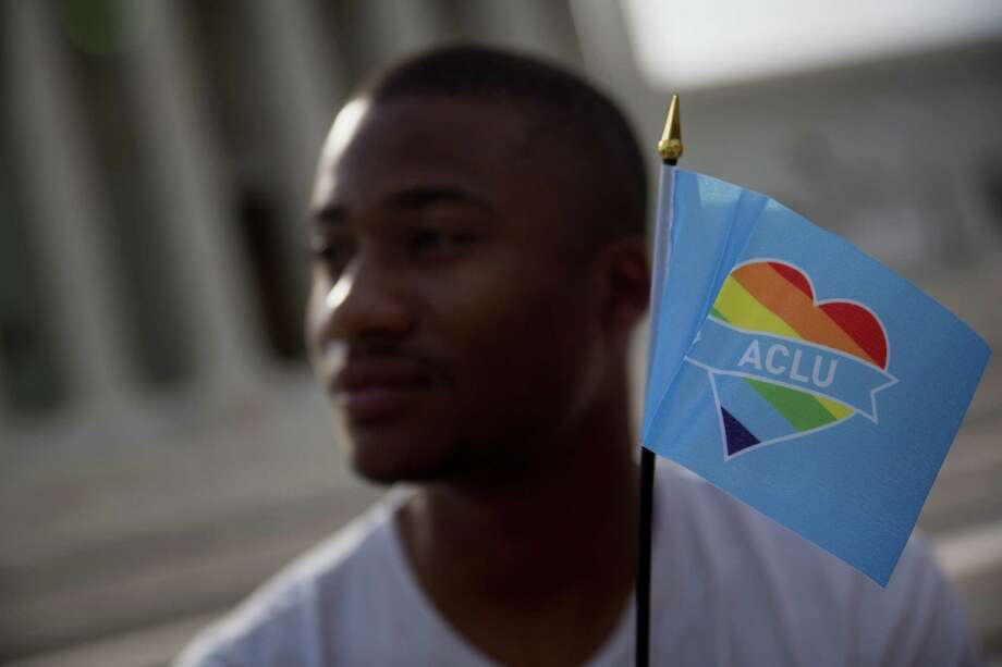 Demonstrator  Michael Abney holds a miniature rainbow American Civil Liberties Union (ACLU) flag outside the U.S. Supreme Court in Washington, D.C., U.S., on Friday, June 26, 2015. Photo: Andrew Harrer, Bloomberg / © 2015 Bloomberg Finance LP