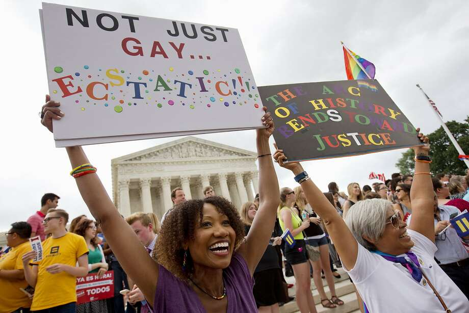 Ikeita Cantu, left, and her wife Carmen Guzman, of McLean, Va., hold up signs as they celebrate outside of the Supreme Court in Washington, Friday June 26, 2015, after the court declared that same-sex couples have a right to marry anywhere in the US. The couple was married in Canada in 2009 when gay marriage was illegal in Virginia. (AP Photo/Jacquelyn Martin) Photo: Jacquelyn Martin, Associated Press