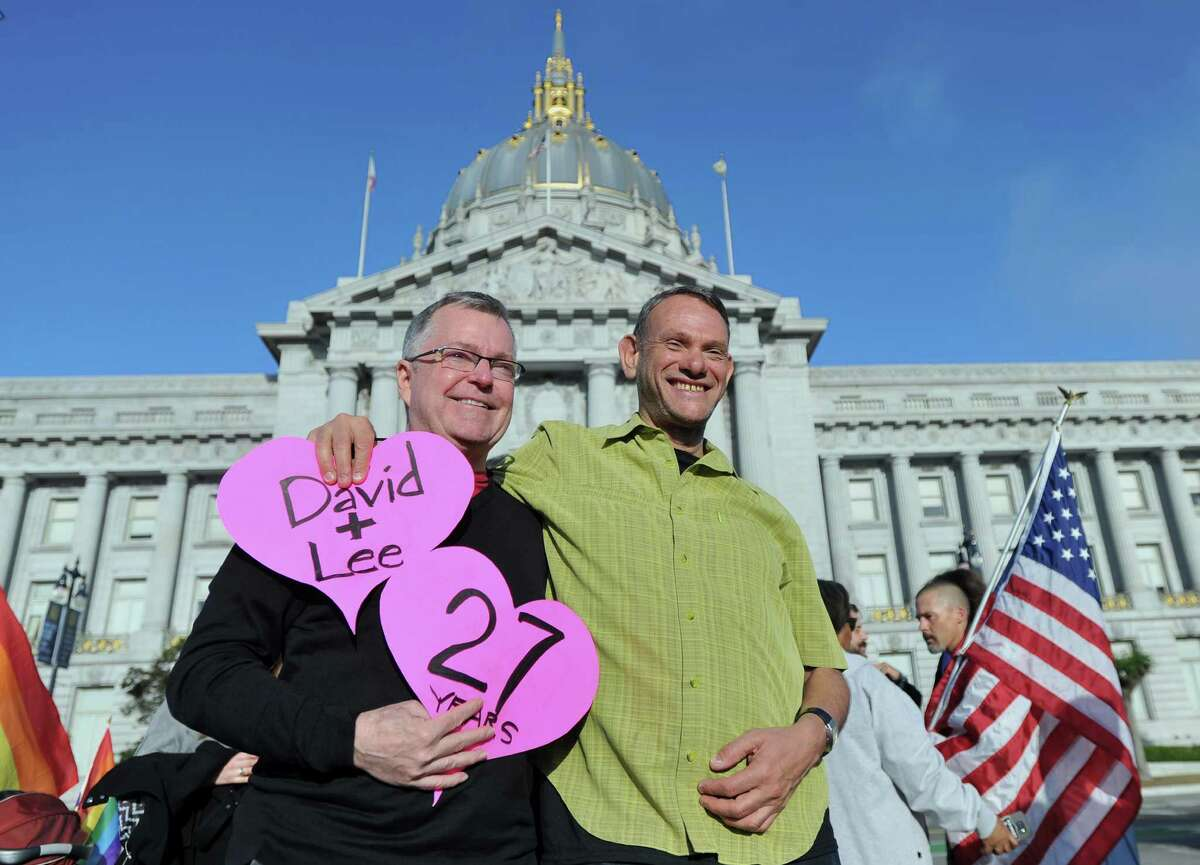 Lee Moulton, left, and David Fink, a couple of 27 years, smile outside of City Hall after the U.S. Supreme Court ruled in favor of same-sex marriage in San Francisco, California, U.S., on Friday, June 26, 2015. Same-sex couples have a constitutional right to marry nationwide, the U.S. Supreme Court said in a historic ruling that caps the biggest civil rights transformation in a half-century. Photographer: Josh Edelson/Bloomberg *** Local Caption *** Lee Moulton; David Fink