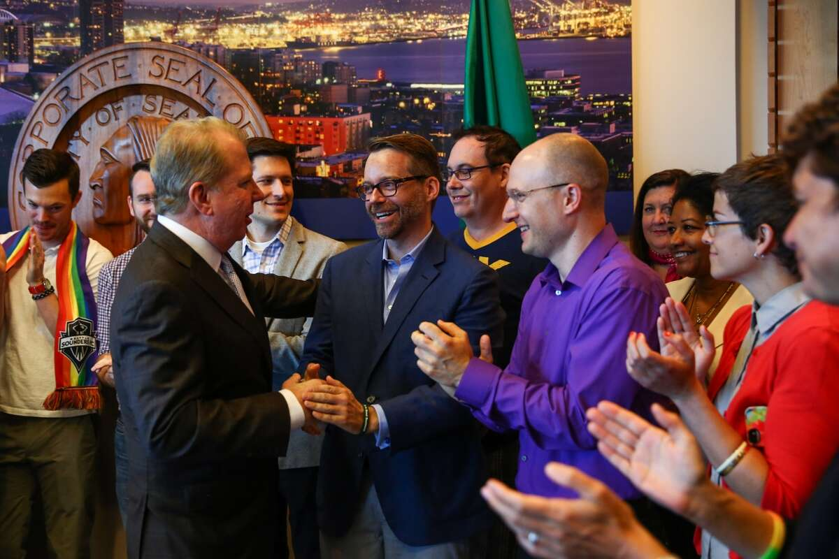 Seattle Mayor Ed Murray shakes hands with Roger Nyhus and other same sex marriage supporters at a city hall event where the mayor talked about the Supreme Count decision allowing same-sex marriage. Nyhus will host a June 29 fundraiser for ex-Vice President Joe Biden.