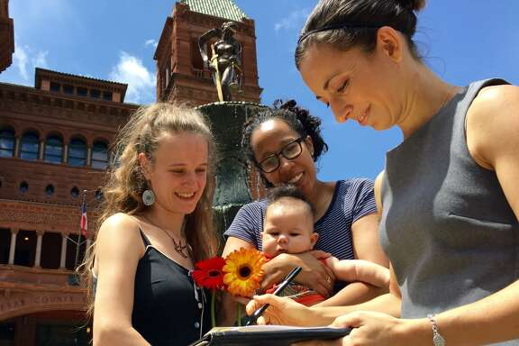 Leilani Long, right, a minister, signs the marriage license after performing a wedding for Gabby Bonar, left, and Liz Moseley, center, hold her son Langston Moseley in front of the Bexar County Courthouse.