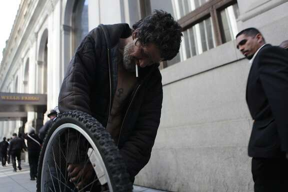 Calap Jayjenkins, 54, works on his bike as San Franciscans pass on by in the Financial District.  He's been homeless for over 30 years.
