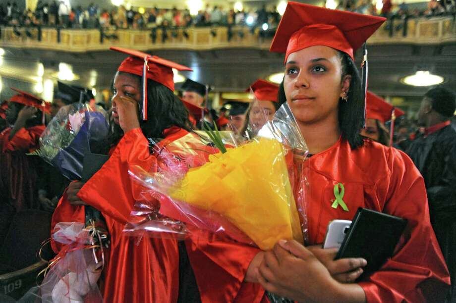 Mareyah Franco, left, wipes her tears as she stands next to her classmate Ceniya Fountain at the conclusion of their graduation ceremony for Schenectady High School at Proctors on Friday, June 26, 2015 in Schenectady, N.Y. (Lori Van Buren / Times Union) Photo: Lori Van Buren / 00032179A