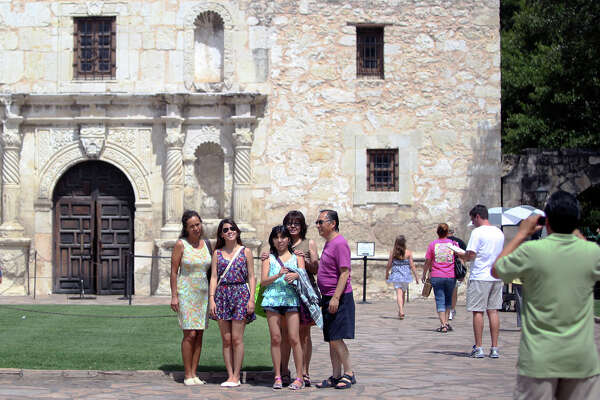 A family poses in front of the Alamo during a 2012 July Fourth visit to the city. UNESCO is expected to decide next week whether the Alamo and the four-mission San Antonio Missions National Historic Park will become the newest World Heritage site — the first in Texas. If it decides to approve the the designation, San Antonio can count on bigger future tourism statistics, leading to more hotel tax revenues and jobs.