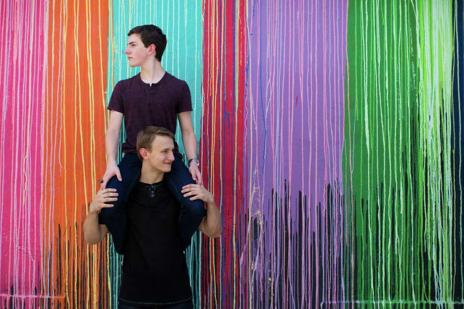 Austin Wallis, 17, left, and his boyfriend, Nicolay Sysyn, also 17, goof around in front of the colorful Biscuit Paint Wall in Montrose. Four months ago, they appeared on a YouTube video that went viral after Wallis was told by his high school principal that he need it to delete all  his social media posts that made reference to his life as a gay teenager. Wallis declined and left the private school. Wallis and Sysyn will ride on the Pride Houston float June 27th. ( Marie D. De Jesus / Houston Chronicle ) Photo: Marie D. De Jesus, Staff / © 2015 Houston Chronicle