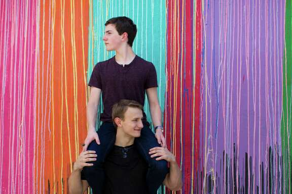 Austin Wallis, 17, left, and his boyfriend, Nicolay Sysyn, also 17, goof around in front of the colorful Biscuit Paint Wall in Montrose. Four months ago, they appeared on a YouTube video that went viral after Wallis was told by his high school principal that he need it to delete all  his social media posts that made reference to his life as a gay teenager. Wallis declined and left the private school. Wallis and Sysyn will ride on the Pride Houston float June 27th. ( Marie D. De Jesus / Houston Chronicle )