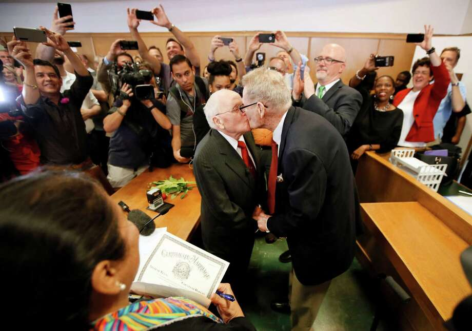 Judge Dennise Garcia, left front, watches as George Harris, center left, 82, and Jack Evans, center right, 85, kiss after being married by Judge Garcia Friday, June 26, 2015, in Dallas. Gay and lesbian Americans have the same right to marry as any other couples, the Supreme Court declared Friday in a historic ruling deciding one of the nation's most contentious and emotional legal questions. Celebrations and joyful weddings quickly followed in states where they had been forbidden. Photo: Tony Gutierrez, Associated Press / AP