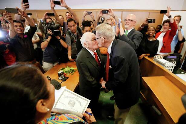 Judge Dennise Garcia, left front, watches as George Harris, center left, 82, and Jack Evans, center right, 85, kiss after being married by Judge Garcia Friday, June 26, 2015, in Dallas. Gay and lesbian Americans have the same right to marry as any other couples, the Supreme Court declared Friday in a historic ruling deciding one of the nation's most contentious and emotional legal questions. Celebrations and joyful weddings quickly followed in states where they had been forbidden.
