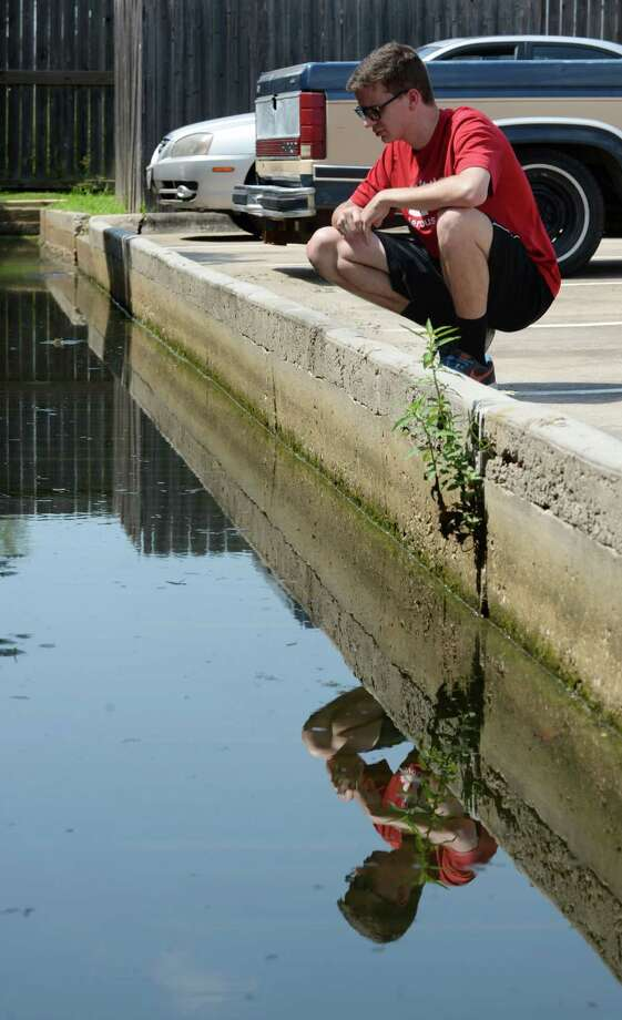 Brad Stodden looks for wildlife in a drainage canal where he was bitten by a coral snake after the Memorial Day floods Wednesday, June 24, 2015, in Shenandoah. ( Jon Shapley / Houston Chronicle ) Photo: Jon Shapley, Staff / © 2015 Houston Chronicle