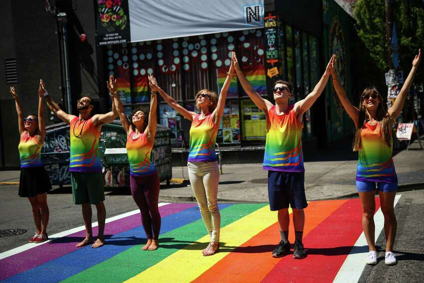 Staff members from Nube9 athletic apparel and others take to a new Capitol Hill rainbow-colored crosswalk after the United States Supreme Court ruled that same-sex marriage is legal in the United States. The historic ruling comes the same weekend that hundreds of thousands will celebrate Pride in Seattle. Photographed on Friday, June 26, 2015.