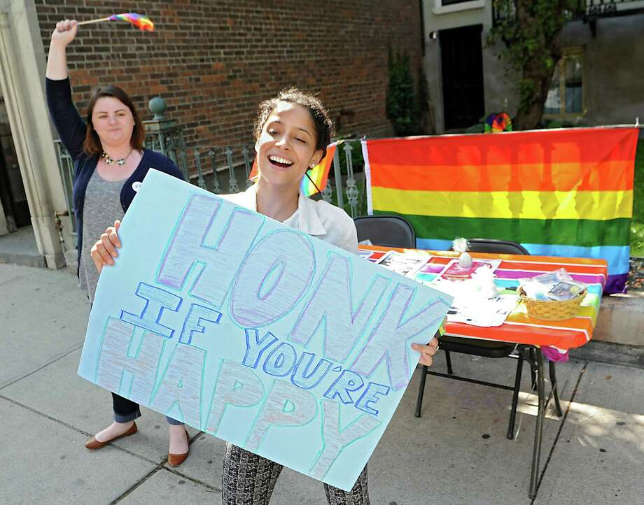 "University at Albany student Tayna Pena of the Bronx holds a sign ""Honk If Your Happy,"" as Abby Jones of Albany waves a flag behind her on Lark St. as they celebrate the  Supreme Court's decision to extend same-sex marriage nationwide on Friday, June 26, 2015, in Albany, N.Y. (Lori Van Buren / Times Union) Photo: Lori Van Buren"
