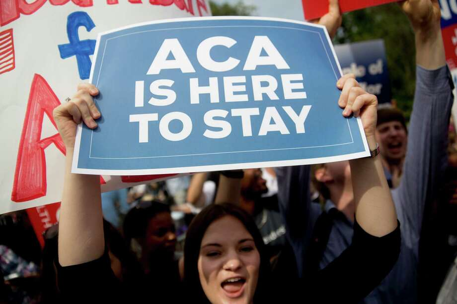 """A demonstrator supporting President Barack Obama's health care law, the Affordable Care Act, holds up a """"ACA is Here to Stay"""" sign after the U.S. Supreme Court saved Obamacare tax subsidies. Texas officials should address the Medicaid gap that is hurting many working Texans. Photo: Andrew Harrer /Bloomberg / © 2015 Bloomberg Finance LP"""