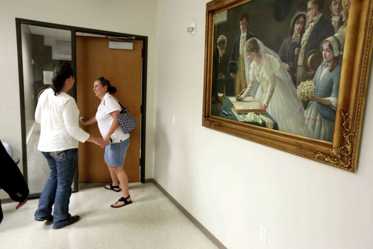 A traditional husband and wife wedding painting hangs on the wall of the County Clerks Office while Carly Kinslow, left, and partner Jenifer Wegley, of Katy, exit after filing for a marriage license at Harris County Civil Courthouse Friday, June 26, 2015, in Houston. The Supreme Court of the United States on Friday ruled that same-sex couples can marry nationwide.