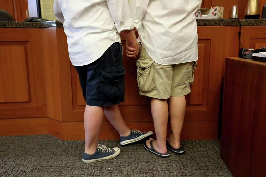 Ashley Creath, left, and Jacquey Creath, of Houston, a couple for nine years, are wed by Judge Kyle Carter, not shown, of the 125 District Court, in the Harris County Civil Courthouse Friday, June 26, 2015, in Houston.